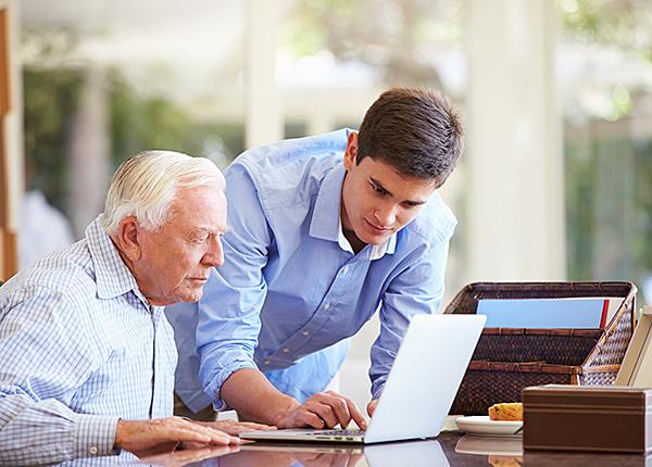 Jonge man helpt oudere man met laptop